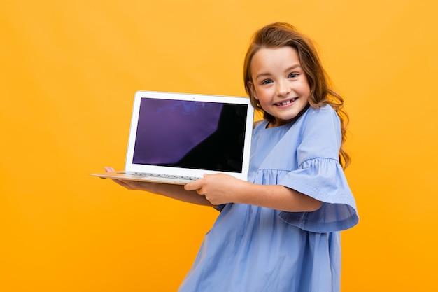 Urocza dziewczyna patrzy na wyświetlacz laptopa z makietą na żółtej ścianie
