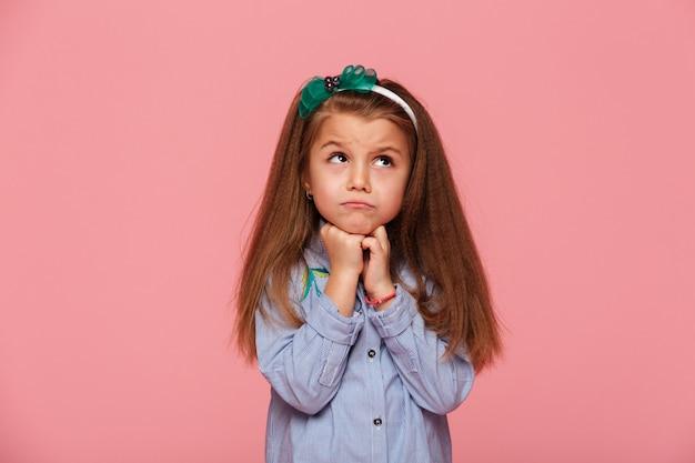 Urocza dziewczyna podpiera głowę z pięściami zdenerwowanymi lub marzącymi