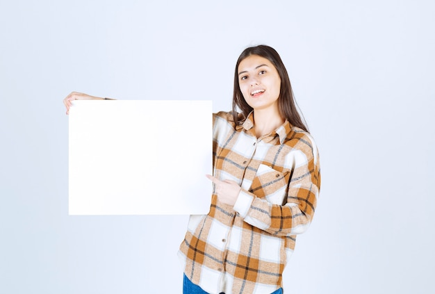 Urocza dziewczyna pokazuje białą dużą pustą kartę na białej ścianie.