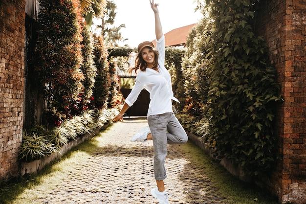 Urocza dziewczyna pokazuje znak pokoju. kobieta w za dużej koszuli i spodniach skacze z uśmiechem na ścieżce z płotem przeplatanym bluszczem.