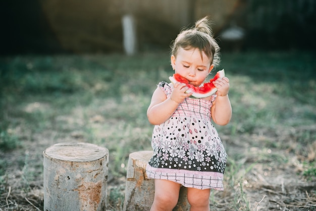Urocza dziewczyna półtora roku, jedząca arbuza na świeżym powietrzu, we wsi na tle drzew z ogonem na głowie