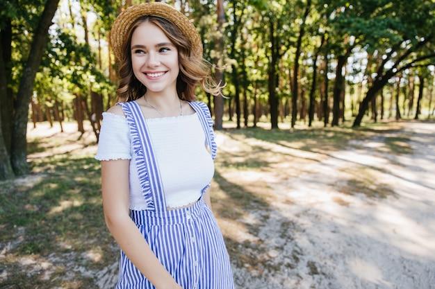 Urocza dziewczyna pozuje z szczęśliwy wyraz twarzy w lesie. beztroska jasnowłosa kobieta bawi się w letni weekend.