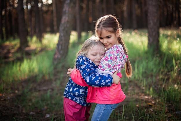 Urocza dziewczyna przytula swoją młodszą siostrę z miłością i czułością podczas spaceru po lesie jesienią, narodowy dzień przytulenia i przyjaźni, swobodny styl życia, plener