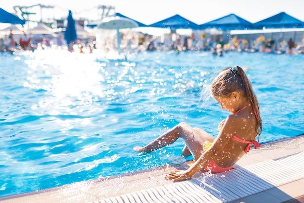 Urocza dziewczyna siedzi na brzegu basenu ze stopami zanurzonymi w czystej, przezroczystej wodzie, ciesząc się ciepłym, jasnym słońcem
