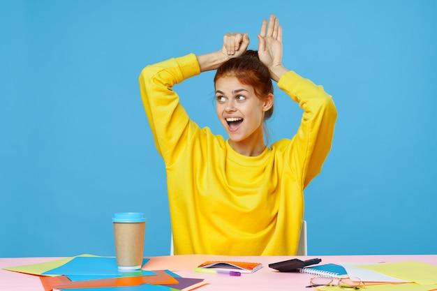 Urocza dziewczyna siedzi przy kreatywnym wielobarwnym stole