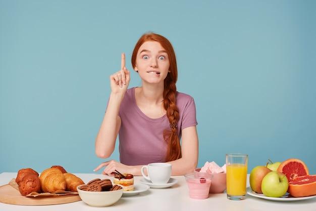 Urocza dziewczyna siedzi przy stole w porze obiadowej, nagle przyszedł na myśl dobry pomysł, uniesiony palec wskazujący