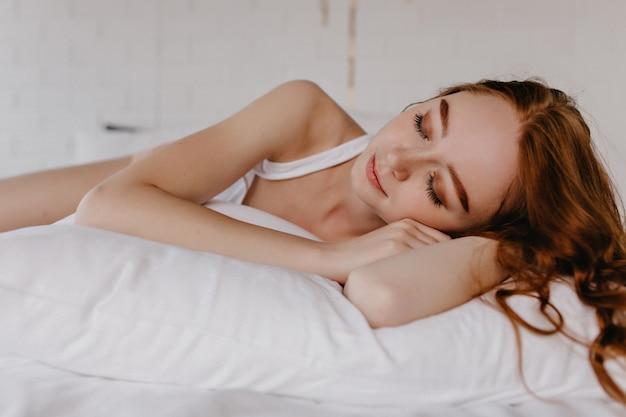 Urocza dziewczyna śpi na poduszce z falowaną fryzurą. kryty zdjęcie zmęczonej imbirowej modelki z makijażem.