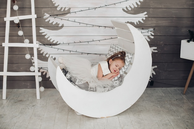 Urocza dziewczyna śpi w łóżku przed malowaną choinką.