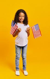 Urocza dziewczyna trzyma amerykańskie flagi