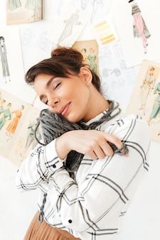 Urocza dziewczyna trzyma przędzę do robienia na drutach blisko twarzy