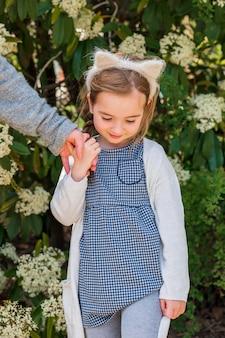 Urocza dziewczyna trzyma rękę matki