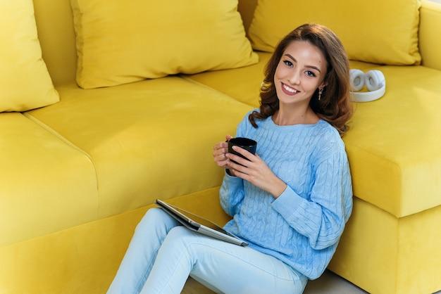 Urocza dziewczyna trzyma w ręce komputer typu tablet, siedzi na podłodze obok nowoczesnej żółtej kanapy i pije kawę w nowoczesnej stylowej kuchni. młoda rozochocona kobieta ma odpoczynek przy wygodnym domem.