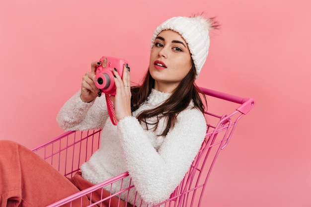 Urocza dziewczyna w białych zimowych ubraniach z różowym aparatem w dłoniach pozuje na odizolowanej ścianie, siedząc w wózku supermarketu.