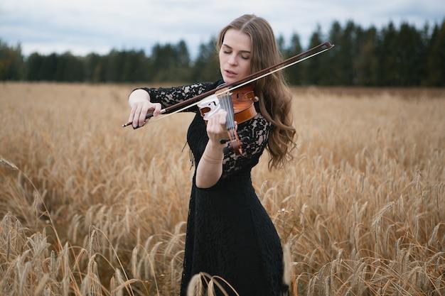 Urocza dziewczyna w czarnej sukience entuzjastycznie grająca na skrzypcach na polu pszenicy
