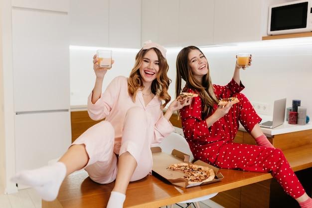 Urocza dziewczyna w czerwonym kombinezonie, pije sok i śmieje się. zabawna brunetka dama je pizzę i wyraża pozytywne emocje.