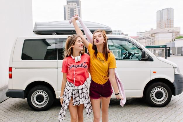 Urocza dziewczyna w dżinsowych szortach z jasnym makijażem pozuje z całowaniem wyrazem twarzy, podczas gdy jej przyjaciółka w różowej koszuli się śmieje