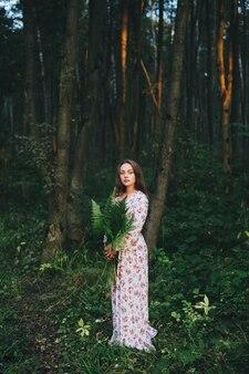 Urocza dziewczyna w kwiecistej sukni siedzi w lesie z bukietem paproci.