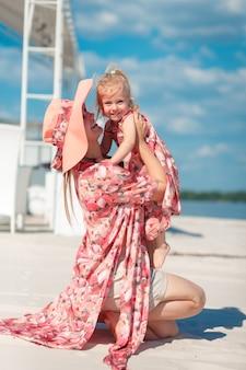 Urocza dziewczyna w lekkiej letniej sukience spaceruje po piaszczystej plaży z córeczką. lubi ciepłe, słoneczne letnie dni.