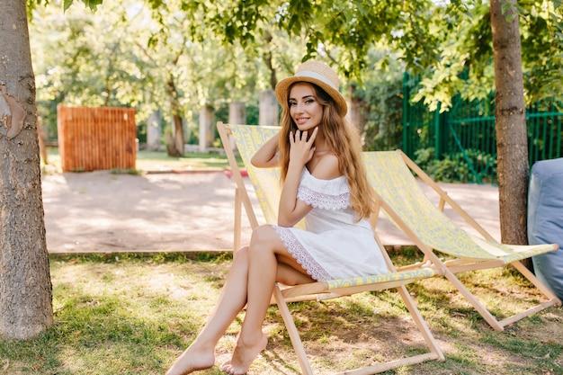 Urocza dziewczyna w łódeczce vintage, myśląca o czymś przyjemnym siedząc w żółtym szezlongu. ładna uśmiechnięta pani w białej sukni pozuje w ogrodzie w weekend.