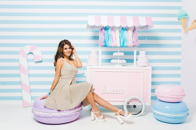 Urocza dziewczyna w modnej sukience i białych butach na obcasie pozowanie w pobliżu cukierni, siedząc na krześle z ciastem i uśmiechając się. kryty portret całkiem młoda kobieta odpoczywa obok kontuaru ze słodyczami na pasiastej ścianie