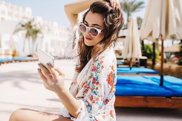 Urocza dziewczyna w modnych białych okularach przeciwsłonecznych pisze wiadomość do przyjaciela, trzymając jej ciemne włosy. portret niesamowitej brunetki młodej kobiety w stylowej koszuli siedzi na zewnątrz z telefonem