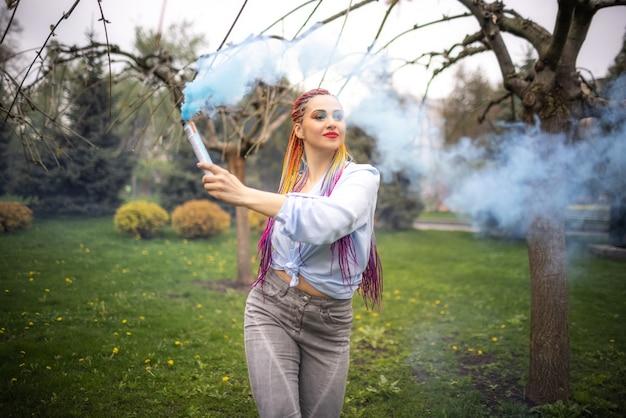 Urocza dziewczyna w niebieskawej koszuli z wyrazistym makijażem i kolorowymi afrykańskimi warkoczami. pozowanie i kręcenie się w gęstym, błękitnym, sztucznym dymie w kwitnącym parku.