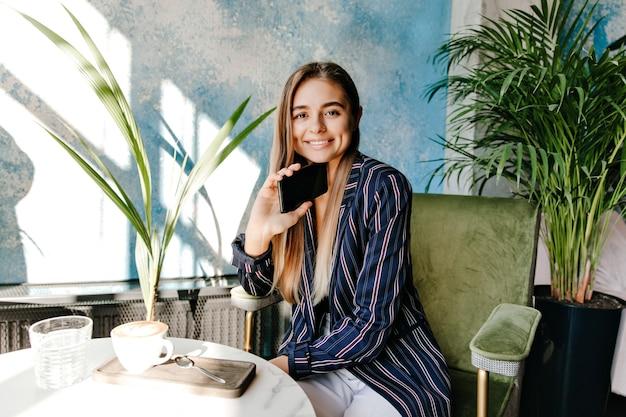 Urocza dziewczyna w niebieskiej kurtce, ciesząc się przerwą na kawę. roześmiana długowłosa kobieta uśmiechnięta w przytulnej kawiarni.