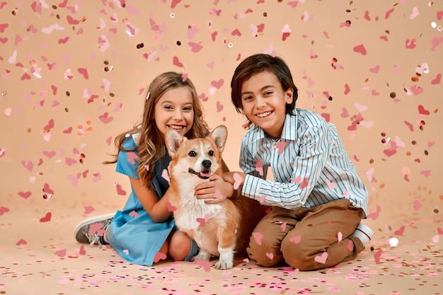 Urocza dziewczyna w niebieskiej sukience i miły chłopak siedzą na podłodze ze śmiesznym psem, na których spadają walentynkowe serduszka konfetti na białym tle