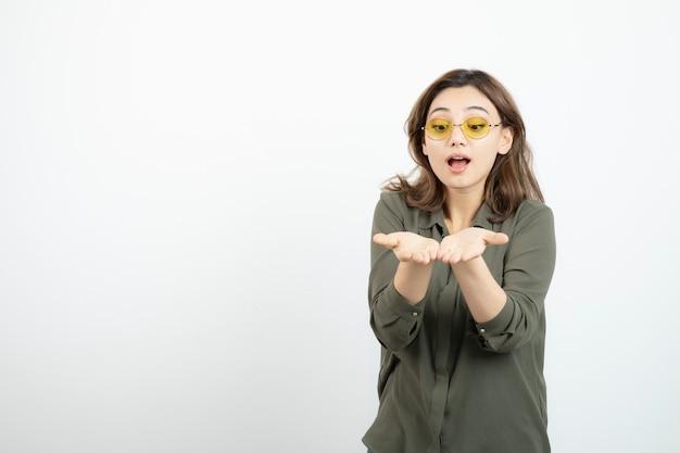 Urocza dziewczyna w okularach otwierając dłonie na białym.