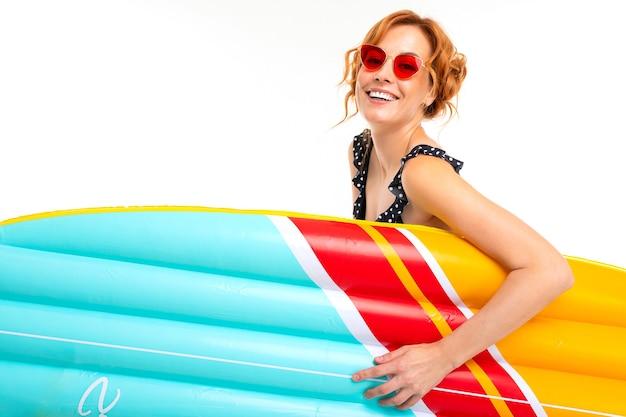 Urocza dziewczyna w okularach retro trzyma deskę surfingową