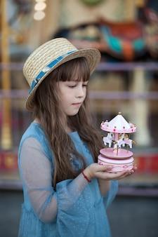 Urocza dziewczyna w parku rozrywki zabytkowa karuzela z zabawkami w rękach małej dziewczynki w kapeluszu