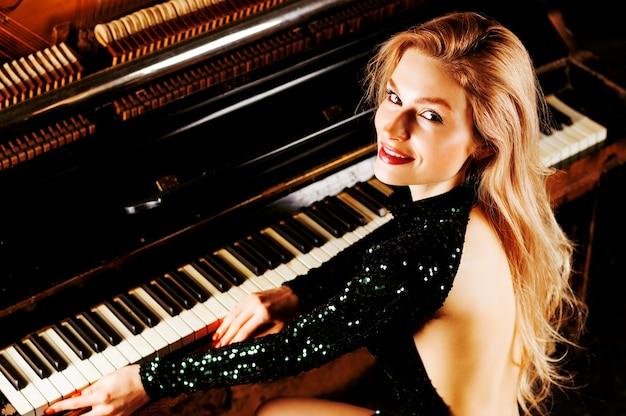 Urocza dziewczyna w stroju wieczorowym pozowanie w pobliżu starego niemieckiego fortepianu. widok z tyłu. różne środki przekazu