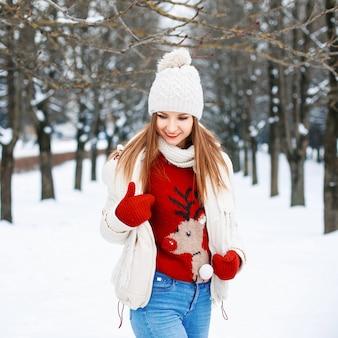 Urocza dziewczyna w stylowym swetrze retro, białej zimowej kurtce i dzianinowej czapce