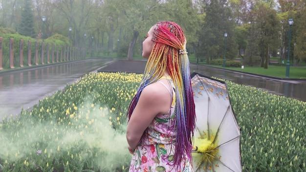 Urocza dziewczyna w sukience z kwiatowym nadrukiem z tęczowymi warkoczami i makijażem. tańczy z parasolką kryjącą się w żółtym dymie na tle klombu z tulipanami