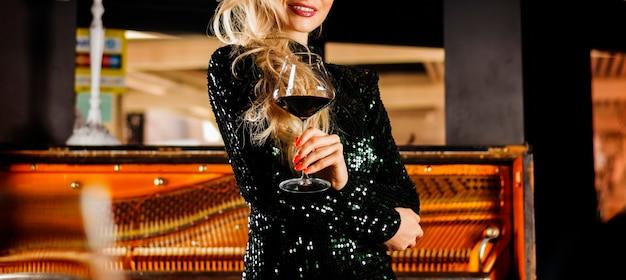 Urocza dziewczyna w wieczorowej sukni cieszy się muzyką i pije czerwone wino. różne środki przekazu