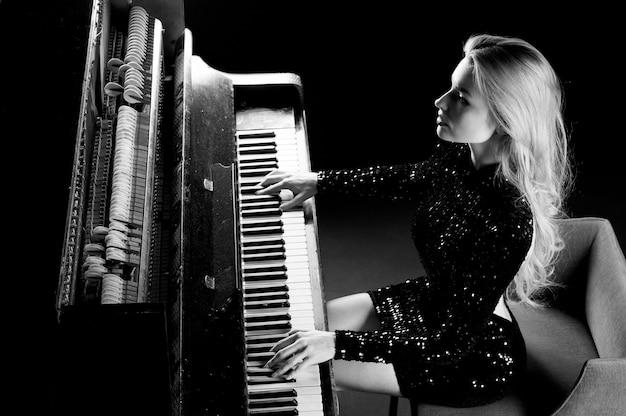 Urocza dziewczyna w wieczorowej sukni gra na starym niemieckim pianinie. widok z góry. media koncepcyjne