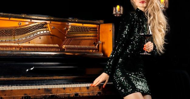 Urocza dziewczyna w zielonej sukni wieczorowej pozuje z kieliszkiem wina w ręku w pobliżu fortepianu retro. różne środki przekazu