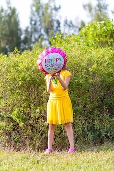 Urocza dziewczyna w żółtej sukience z kolorowym balonem z okazji urodzin w kształcie kwiatka. szczęśliwe dziecko na zewnątrz