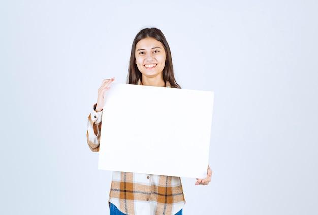 Urocza dziewczyna z białym dużym pustym pozowanie na białej ścianie.