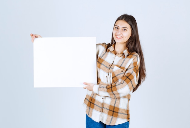 Urocza dziewczyna z białym dużym pustym stojącym nad białą ścianą.
