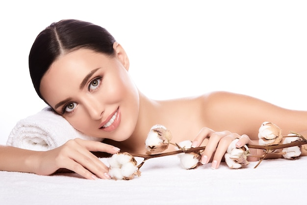 Urocza dziewczyna z brązowymi włosami związanymi z tyłu, czystą, świeżą skórą, dużymi oczami i nagimi ramionami pozuje z kwiatem i ręcznikiem na białej ścianie