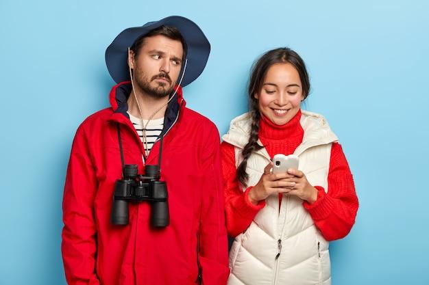 Urocza dziewczyna z długim warkoczem, ubrana w sweter i białą kamizelkę, wysyła zdjęcia z podróży do znajomego, dzieli się wrażeniami z biwakowania i znudzony facet w czapce i kurtce, lornetka na szyi zmęczona po chodzeniu