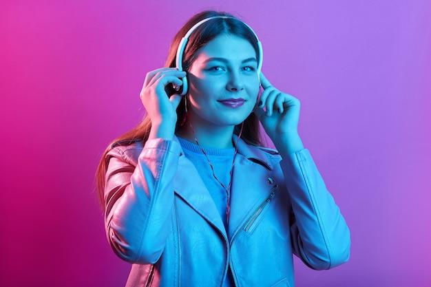 Urocza dziewczyna z długimi włosami wygląda na szczęśliwą, oszałamiającą europejkę relaksującą w słuchawkach, słuchając ulubionej muzyki
