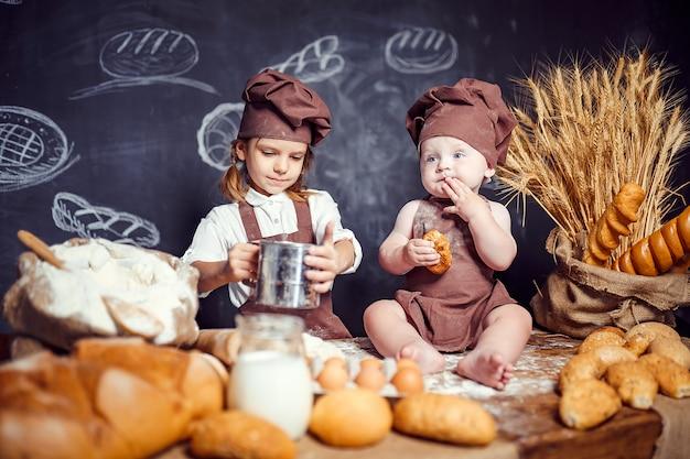 Urocza dziewczyna z dzieckiem na stołowym kucharstwie