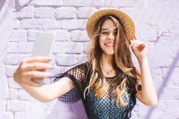 Urocza dziewczyna z eleganckim naszyjnikiem robiącym selfie przed starą białą ścianą