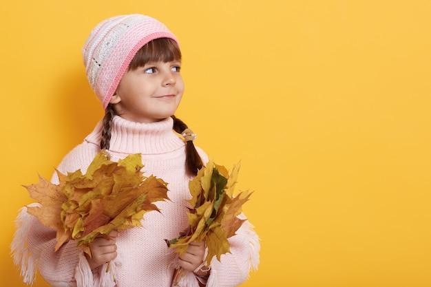 Urocza dziewczyna z jesiennych liści w obu rękach, dziecko patrząc na bok z uśmiechem, pozowanie na białym tle na żółtej ścianie