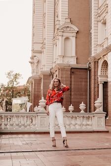Urocza dziewczyna z kręconymi włosami macha idąc ulicą i rozglądając się z uśmiechem. dziewczyna na tarasie ulicy patrząca w kamerę blondynka w europie na balkonie