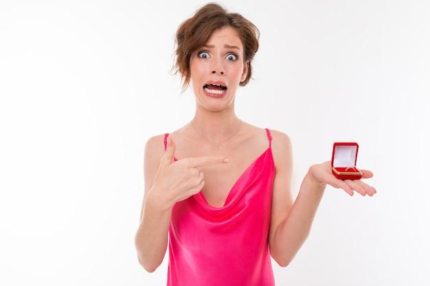 Urocza dziewczyna z niedowierzaniem z makijażem w różowej sukience pokazuje pudełko z pierścieniem na białej ścianie