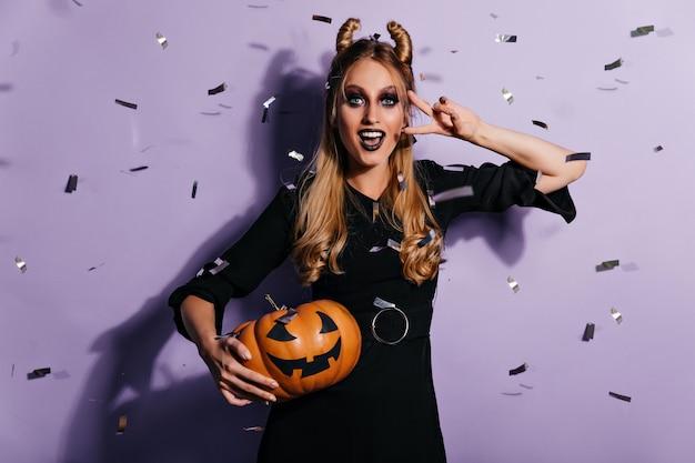 Urocza dziewczyna z przerażającym makijażem, uśmiechając się na fioletowej ścianie. błogi blond kobieta trzyma dyni halloween.