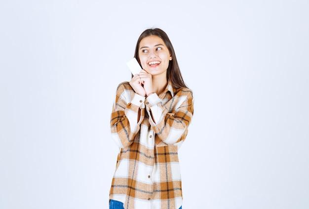 Urocza dziewczyna z pustej wizytówki stojącej na białej ścianie.